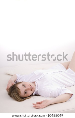 Lazy day. An attractive young woman relaxing on bed