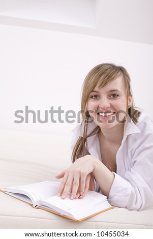 Lazy hours. Beautiful young woman relaxing with book.