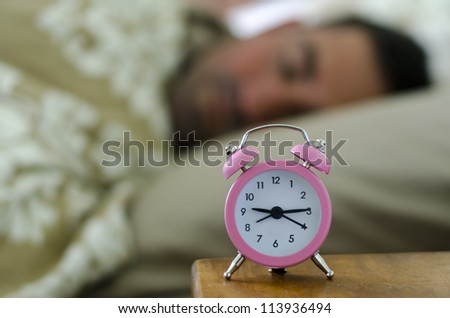 Lazy man lying in bed and sleep in during the morning. - stock photo