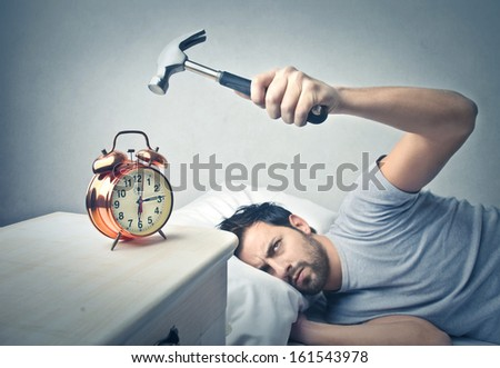 lazy man splits alarm clock with hammer - stock photo