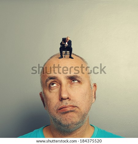 lazy man with small angry businessman on his head - stock photo