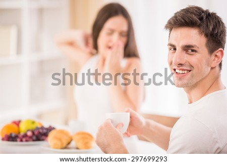 Lazy morning in the kitchen. Young attractive man drinking tea while his sleepy girlfriend making yawn.