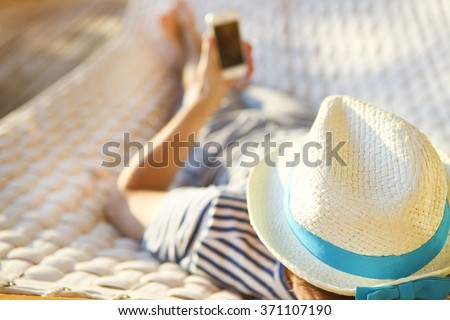 Lazy time. Man in hat in a hammock with mobile phone on a summer day - stock photo