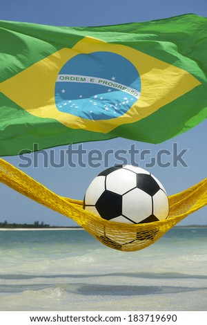 Lazy tired football soccer ball relaxing in beach hammock with Brazilian flag - stock photo