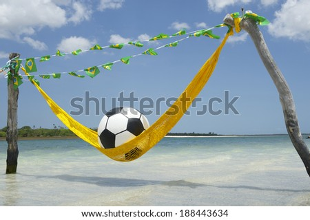 Lazy tired football soccer ball relaxing in beach hammock with Brazilian flag bunting - stock photo