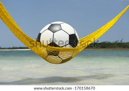 Lazy tired football soccer ball relaxing in Brazilian beach hammock - stock photo