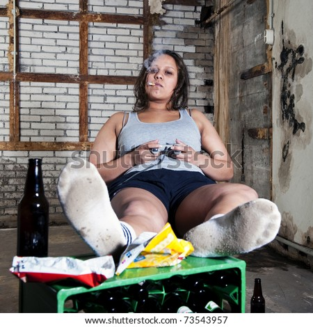 Lazy woman, in an unkept room, looking sleazy with a cigarette in her mouth, playing video games