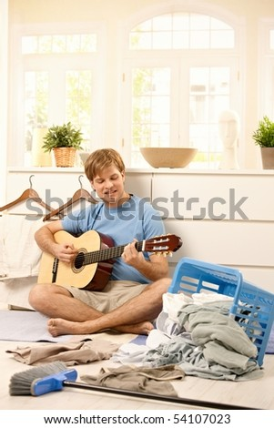 Lazy young guy playing guitar sitting on floor instead of washing laundry or sweeping. - stock photo