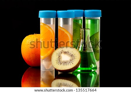 Lb tubes filed with liquid of with fruits parts on black background. - stock photo