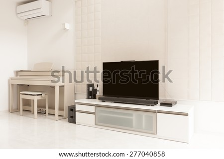 LCD(internet) TV, storage, piano(an electronic organ), art wall at the white living room on the white marble. - stock photo