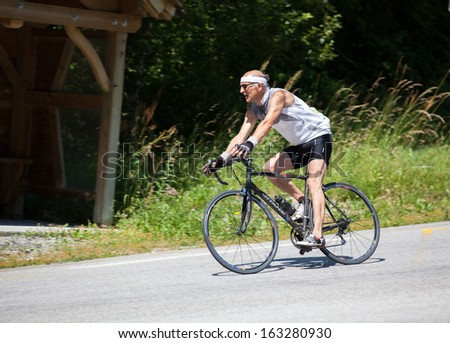 Le Garcin, FRANCE - July 6: Amateur mature Racer in The Marmotte Race, French Alps, July 6, 2013 covering 174km, including Col du Glandon, Col du Galibier, the most feared Tour de France mountains. - stock photo