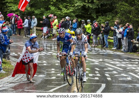 LE MARKSTEIN, FRANCE - JUL 13:A fan cheers a group of three cyclists on the road to mountain pass Le Markstein during the stage 9 of Le Tour de France on July 13, 2014. - stock photo