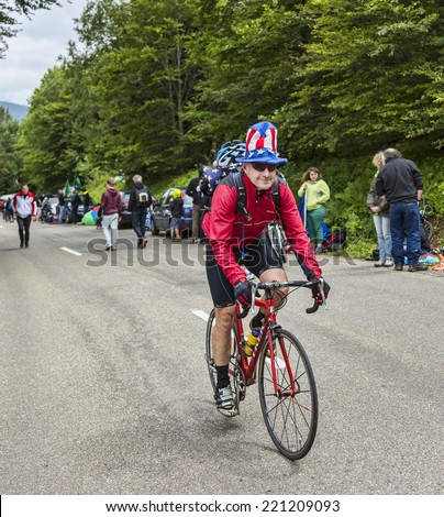 LE MARKSTEIN, FRANCE - JUL 13: Funny amateur cyclist wearing a US flag hat climbing the road to the mountain pass Le Markenstein during Le Tour de France on July 13, 2014.