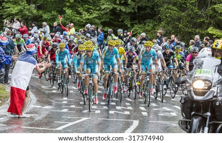 LE MARKSTEIN, FRANCE - JUL 13:The peloton riding on the road to mountain pass Le Markstein during the stage 9 of Le Tour de France on July 13, 2014 - stock photo