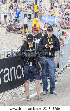 LE MONT VENTOUX, FRANCE-JUL 14:Two young men using modern electronic devices to transmit data from the road to Mont Ventoux during the stage 15 of Le Tour de France on July 14 2013.