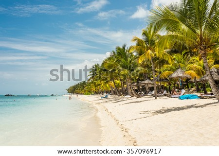 LE MORNE, MAURITIUS - DECEMBER 7, 2015: People relax on the Beach at Le Morne Brabant, one of the finest beaches in Mauritius and the site of many hotels and tourism facilities.