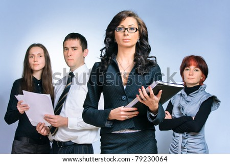 Leader and her team, Young attractive business people with focus only on businesswoman in the middle - stock photo