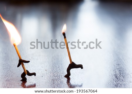 Leader concept. Two burning matches run the table. - stock photo