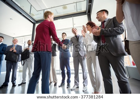 Leader congratulate to his worker and give him recognition for success - stock photo