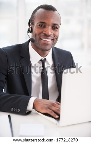 Leader of support team. Handsome young African man in formalwear and headset working on laptop and smiling at camera - stock photo