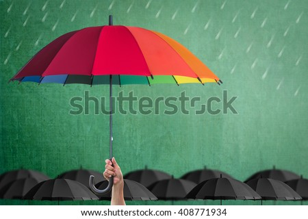 Leader person's hand holding rainbow umbrella distinctive unique among black color other on green school chalkboard background: Life-health Insurance protection, Business financial leadership concept  - stock photo