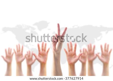 Leader's two fingers V victory sign among blur hands crowd group:: Many people blurred palms raising up upward isolated on white sky background map: World participation, leadership, volunteer concept