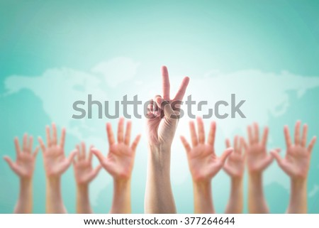 Leader's two fingers victory sign among blur hands crowd group: Many people blurred palms raising up upward on vintage blue sky background map: World participation, leadership volunteer concept: V day - stock photo