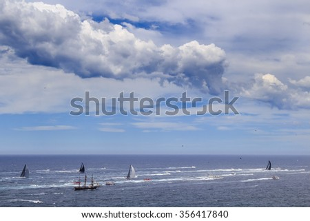 Leaders of Sydney Hobart yacht race getting away ahead of main group of yachts surrounded by spectator boats under cloud in open ocean near Sydney - stock photo