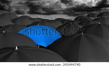 Leadership and innovation concept of a blue umbrella in a crowd of black ones - stock photo