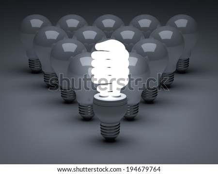 Leadership concept, One glowing Eco energy saving light bulb standing in front of unlit incandescent bulbs over dark background - stock photo