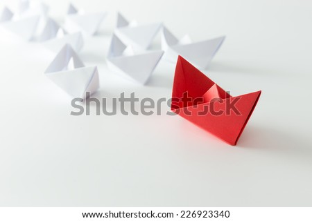 Leadership concept using red paper ship among white - stock photo