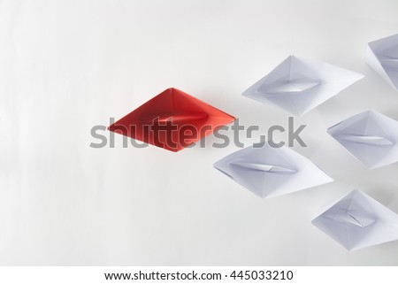 Leadership concept with red paper ship leading among white.