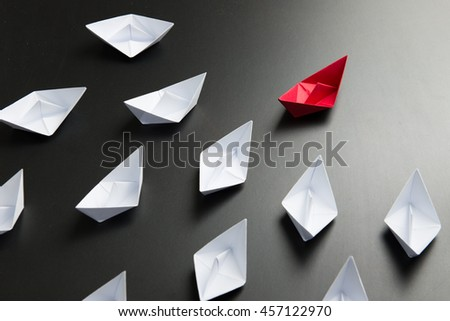Leadership concept with red ship leading among the white