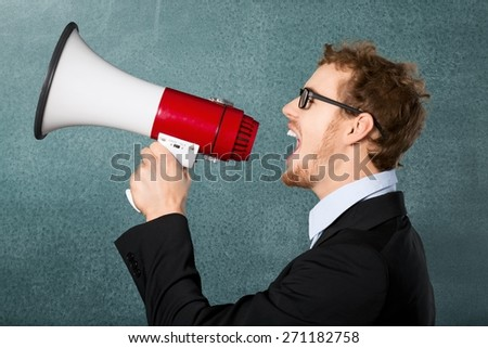 Leadership. Male Professor Shouting Though Megaphone Against Chalkboard - stock photo