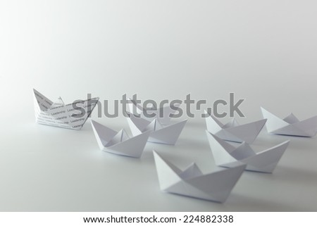 Leadership origami boat leading group of white boats