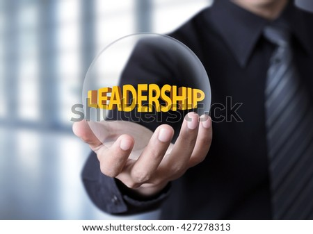 "Leadership symbol in businessman hand, Businessman showing ""Leadership"" text in crystal ball"
