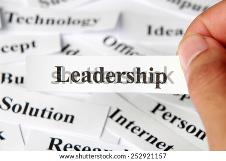 Leadership word paper in hand with the background of other words.