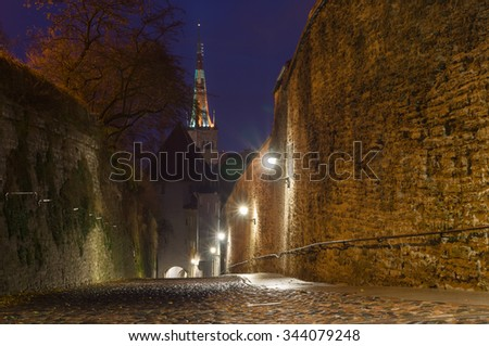 Leading down Pikk Jalg street illuminated by night with view on Oleviste church, Tallinn, Estonia - stock photo