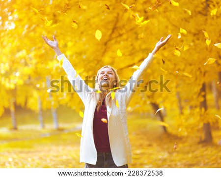 Leaf fall, colorful photo happy positive expression woman having fun in the autumn park - stock photo
