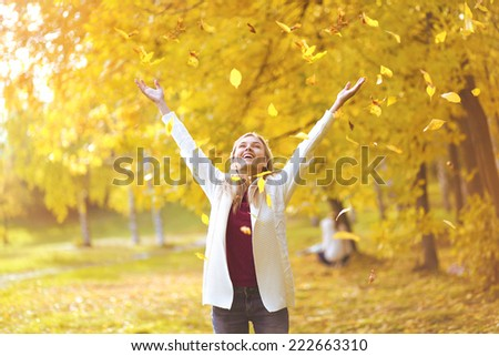 Leaf fall, happy woman in the autumn park - stock photo