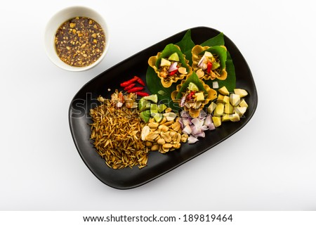 Leaf wrapped bite size appetizer, grated coconut, ginger, shallots, peanuts, dried shrimps, lime, chillies and edible tree leaves, Miang Kum, Traditional Thai food.  - stock photo