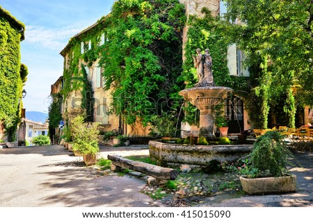 Leafy town square with fountain in a picturesque village in Provence, France - stock photo
