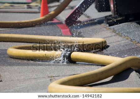 leaking fire hose - stock photo