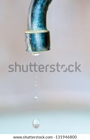 Leaking water drops from the unturned tap - stock photo