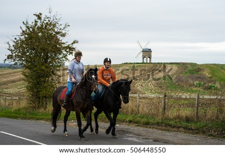 Leamington SPA, UK - OCTOBER 28, 2016: English Couple are riding horses at road, and amazing background with Chesterton Windmill