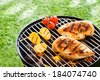 Lean healthy chicken breasts grilling over the hot coals on a portable BBQ with fresh tomatoes and potatoes for a healthy low fat meal - stock photo