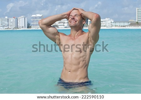 Lean muscular shirtless Caucasian man with abs smiles and pulls hair back while standing in beautiful shallow tropical sea with large resorts in background - stock photo