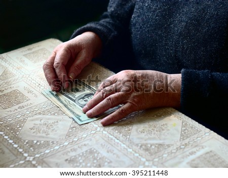 Lean purse. Old woman's hands and dollar bills on table, contrast shot, selective focus, very shallow DOF. Toned image. - stock photo