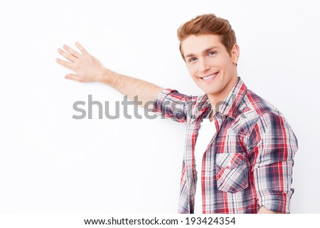 Leaning at copy space. Cheerful young man touching white wall with hand and looking at camera - stock photo