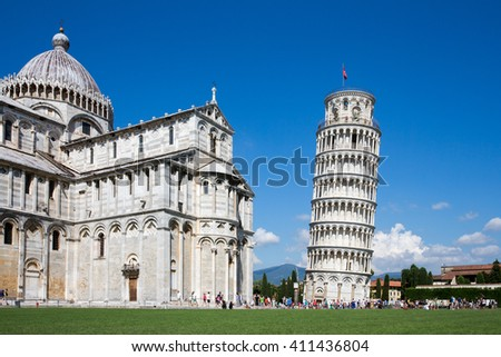 Leaning Tower of Pisa and Pisa Cathedral in Italy with unrecognizable tourists for scale.  Concepts could include architecture, travel, European history, others. - stock photo